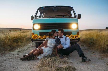 Photo pour Un couple de jeunes mariés est amoureux d'une minifourgonnette rétro - image libre de droit