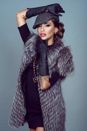 Portrait of a beautiful glam model wearing silver fox jacket.