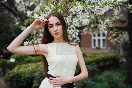 Beautiful girl near magnolia