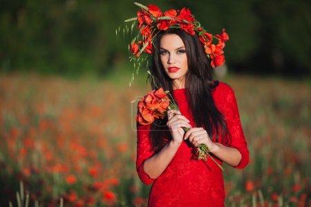 Photo pour Jeune belle fille dans le champ de coquelicots rouges - image libre de droit