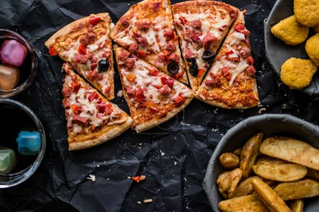 Pizza slices with potato wedges , nuggets and beverage on a black surface (Fast food concept)