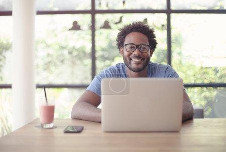 Photo pour Graphiste travaillant au café avec un ordinateur portable sur un bureau en bois. - image libre de droit