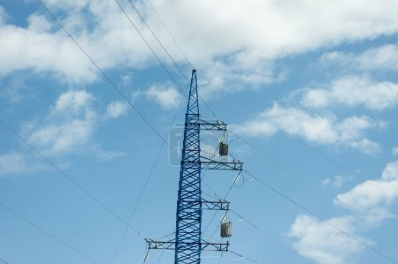 Photo for High voltage pole against blue cloudy sky - Royalty Free Image