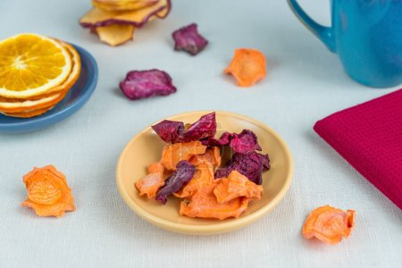 Photo for Healthy food organic nutrition. Sliced and dried apple, orange, carrot and beetroot  and cup of tea on textile tablecloth. - Royalty Free Image