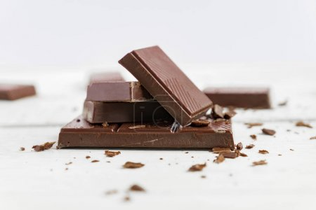 Photo for Chocolate bars on wooden table. Broken pieces of dark chocolate. Food background - Royalty Free Image