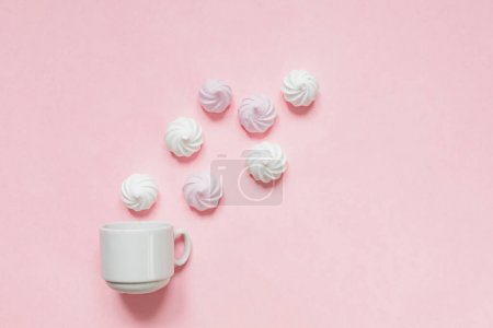 Photo for Top view of white and pink twisted meringues  and coffee cup on pink background. French dessert prepared from whipped with sugar and baked egg whites. Greeting card with copy space - Royalty Free Image