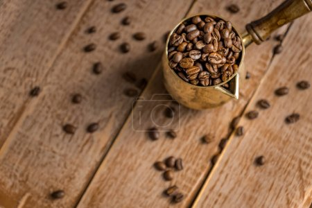 Photo for Close up of fresh roasted coffe beans in  cezve (traditional turkish coffee pot) on wooden table. - Royalty Free Image