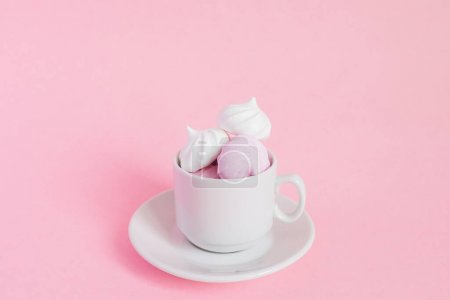 Photo for White and pink twisted meringues in a small porcelain coffe cup on pink background. French dessert prepared from whipped with sugar and baked egg whites. Greeting card with copy space - Royalty Free Image