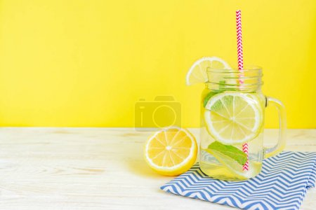 Photo for Mason jar glass of homemade lemonade with lemons, mint and red paper straw on wooden rustic background. Summer refreshing beverage. - Royalty Free Image