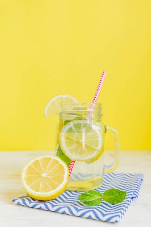 Photo for Citrus lemonade water with sliced lemon and mint, healthy and detox water drink in summer on yellow background. Summer bright backdrop with copy space - Royalty Free Image