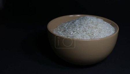 Photo for White uncooked rice in a beige bowl with scattered grains nearby on a black background - Royalty Free Image