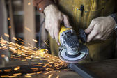 Custom furniture worker grinds weld seam on steel frame.