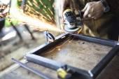 Custom furniture worker grinds welding seams on steel.