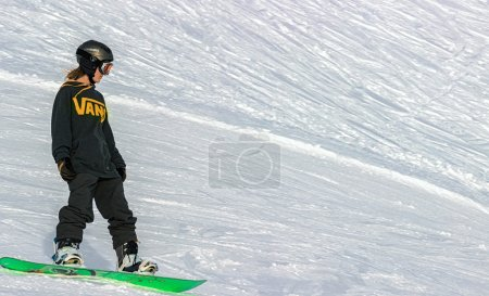 A woman on a snowboard sliding down the mountain