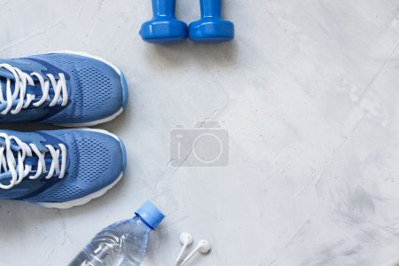 Flat lay sport shoes, bottle of water, dumbbells a...