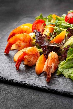Photo pour Salade fraîche aux crevettes sur une assiette noire. Fond en bois noir - image libre de droit