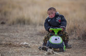Mongol  boy riding his toy car