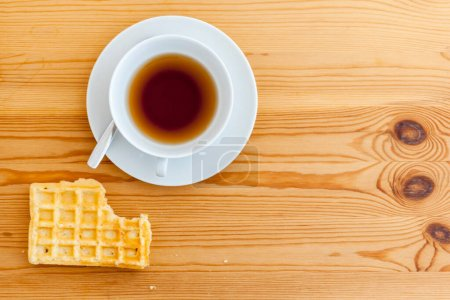 Photo for Wooden table with white cup with saucer and spoon as well as lying waffle with bite mark in top view. - Royalty Free Image